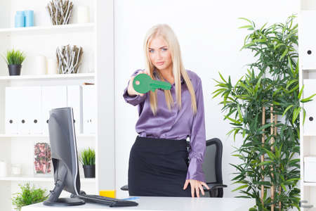 the young woman at office holds big a green key photo