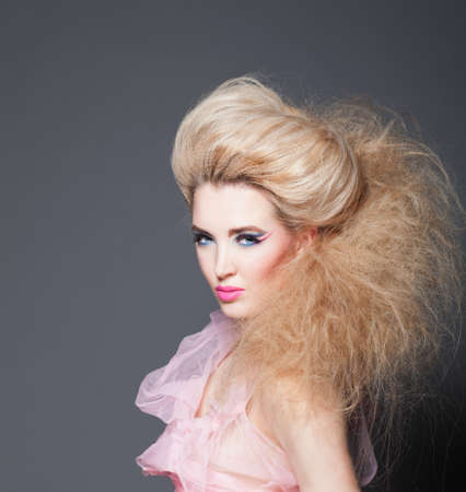 Beautiful model the blonde with a creative hairdress and a make-up photo