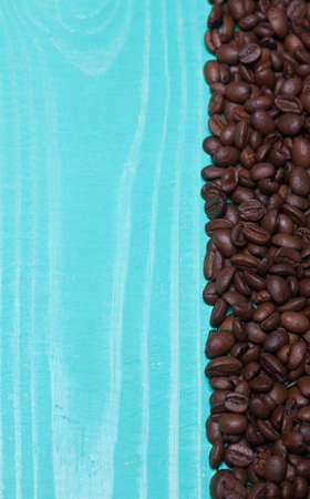 Background turquoise wooden plank with coffee beans photo