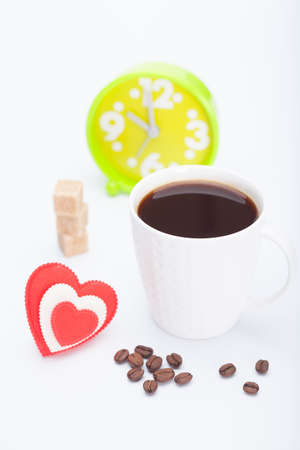 beautiful white cup, coffee, hearts with an alarm clock on a white background photo