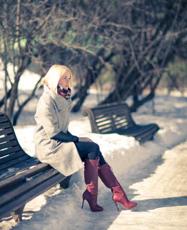 Beautiful young blond woman sitting on a bench in winter coat and red boots. Winter sunny evening. photo