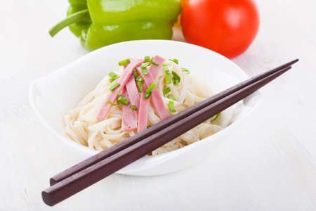 Tasty noodles with ham green onions in a beautiful white bowl on a white wooden background. Peppers and tomatoes.