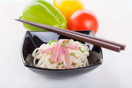 Tasty noodles with ham green onions in a beautiful black bowl on a white wooden background. Pepper and tomatoes. photo