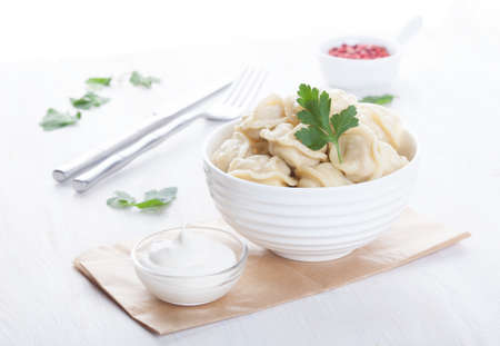 appetizing pelmeni in a beautiful white drinking bowl with sauce and spices