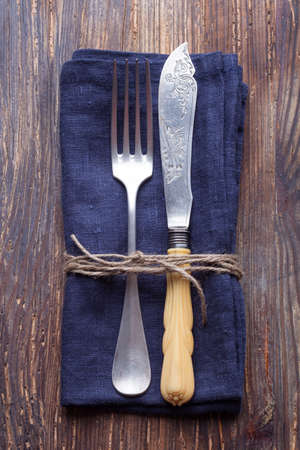 vintage fork and knife a blue napkin on a vintage wooden board Stock Photo - 25853804