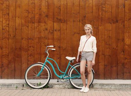 ビンテージ緑の自転車近くに立っている長い髪の若いセクシーなブロンドの女の子がある楽しさと良い気分カメラで探していると笑みを浮かべて 写真素材