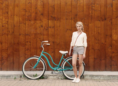 Young sexy blonde girl with long hair standing near vintage green bicycle have fun and good mood looking in camera and smiling