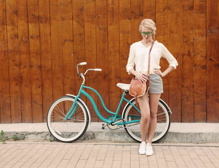 Young sexy blonde girl is standing near the vintage green bicycle with brown vintage bag in green sunglasses.