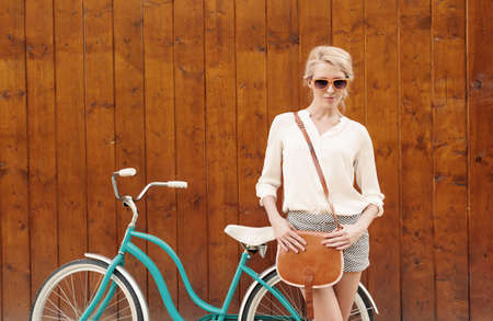 Young sexy blonde girl is standing near the vintage green bicycle with brown vintage bag in orange sunglasses.