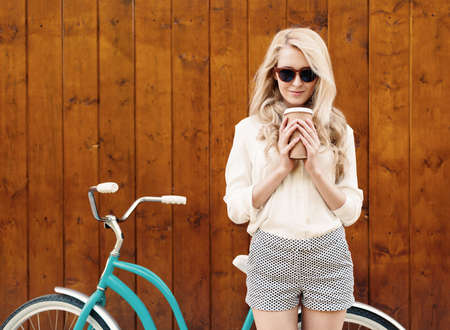 lifestyle outdoors: young sexy blonde girl with long hair in sunglasses standing near vintage green bicycle and holding a cup of coffee