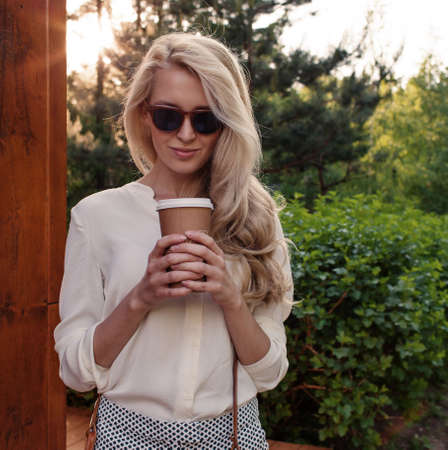 Young sexy blonde girl with long hair in sunglasses holding a cup of coffee have fun and good mood looking in camera and smiling