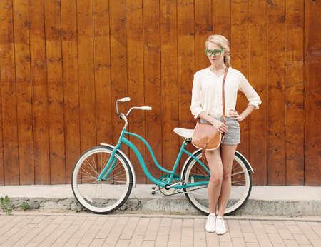 若いセクシーなブロンドの女の子はグリーンのサングラスで茶色のビンテージ バッグ ビンテージ グリーン自転車の近くに立っています。