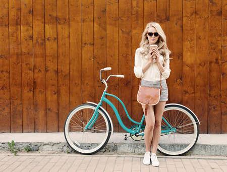 Chica rubia atractiva joven con el pelo largo con una bolsa marrón de la vendimia en gafas de sol de pie cerca de la bicicleta verde del vintage y la celebración de una taza de café, tiene el estado de ánimo de diversión y de buen aspecto en la cámara y sonriendo
