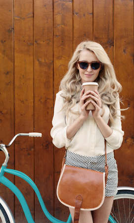 Young sexy blonde girl with long hair with brown vintage bag in sunglasses standing near vintage green bicycle and holding a cup of coffee, have fun and good mood looking in camera and smiling