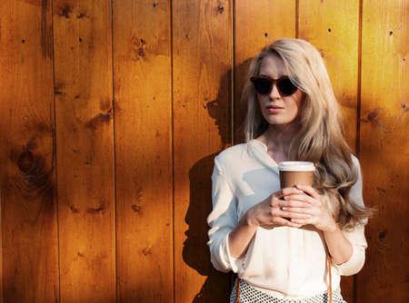 一杯のコーヒーを保持しているサングラスに長髪の若いセクシーなブロンドの女の子が柔らかな光を夜の楽しみ