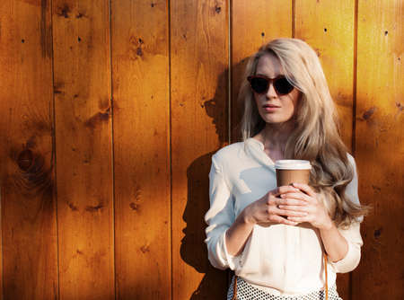 Young sexy blonde girl with long hair in sunglasses holding a cup of coffee have fun evening soft sunlight