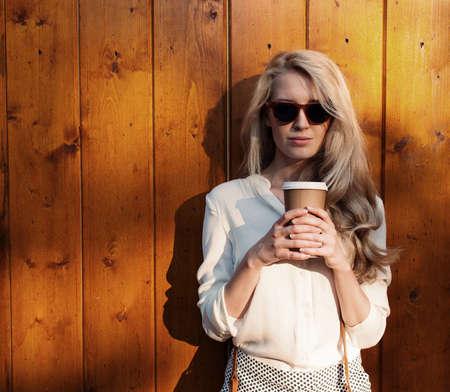 一杯のコーヒーを保持しているサングラスに長髪の若いセクシーなブロンドの女の子がある楽しさとカメラで見て良い気分と smilingevening 柔らかな光