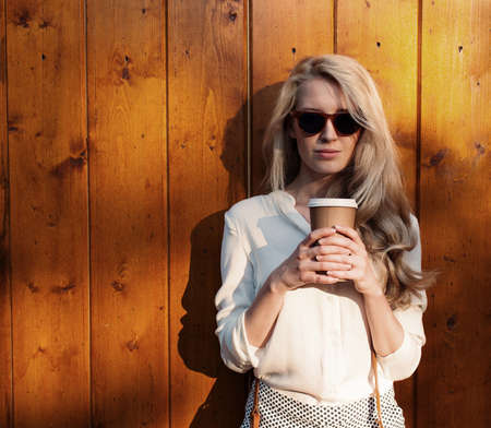 Young sexy blonde girl with long hair in sunglasses holding a cup of coffee have fun and good mood looking in camera and smilingevening soft sunlight 版權商用圖片