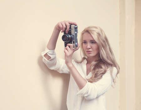 ビンテージ カメラ片手で長い髪とセクシーな金髪の美しい