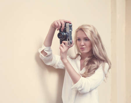beautiful sexy blonde with long hair with vintage camera in hand