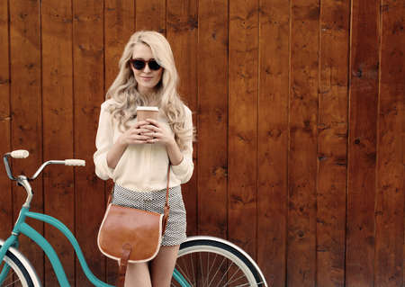 spring fashion: Young sexy blonde girl with long hair with brown vintage bag in sunglasses standing near vintage green bicycle and holding a cup of coffee, have fun and good mood looking in camera and smiling