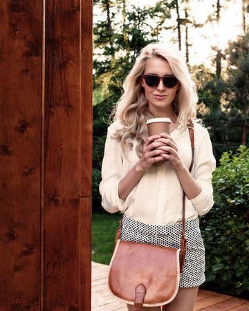 コーヒーのカップを保持している茶色のビンテージ バッグとサングラスでは長い髪を持つ若いセクシーなブロンドの女の子がある楽しさと良い気分