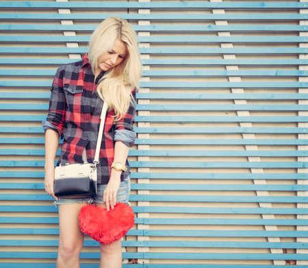 悲しい少女の赤いハートと色の木板の壁付近のスタンドを保持 写真素材