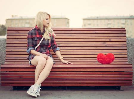 mujeres tristes: Muchacha triste sola que se sienta en un banco cerca de un gran corazón rojo Foto de archivo