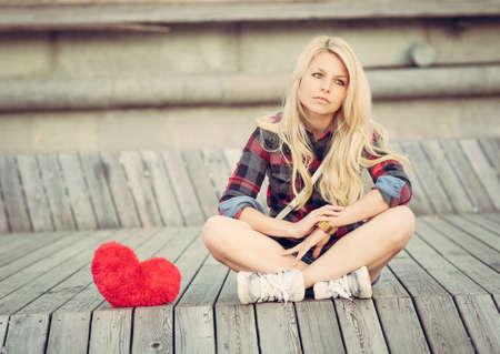 大きな赤いハートの近くに木の板の上に座って悲しい孤独な少女