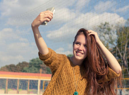 Beautiful redheaded girl doing a selfie outdoor photo