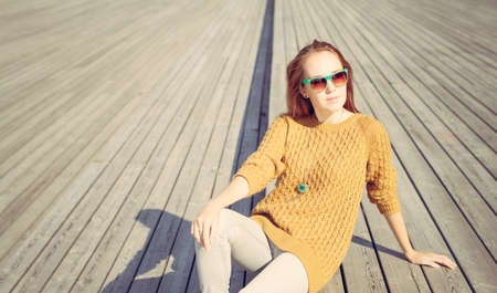 Beautiful redheaded girl in jeans sits on wooden planks photo