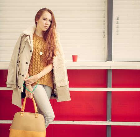 手でファッショナブルなバッグ美しい赤毛の少女は閉じた屋外カフェの近くの価値があります。