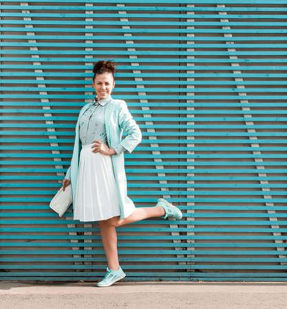色の木板の壁近くに美しいブルネット ヒップ スタイルの女の子が立っています。 写真素材