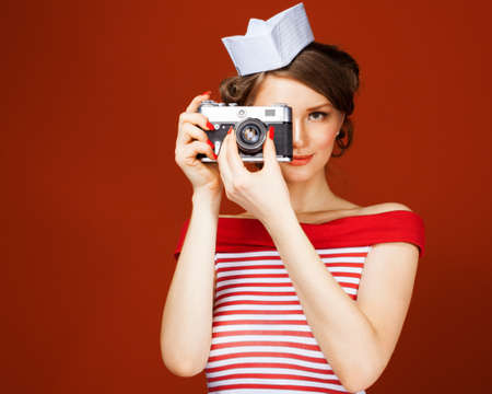 Beautiful pin-up girl holding a vintage camera and directs it straight to the camera. Red background, close up