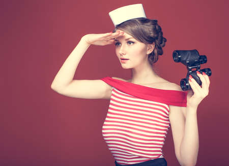 beautiful girl sailor with a vintage binoculars and looks into the distance Banque d'images