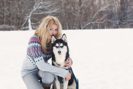 Winter portrait of a beautiful young girl with a Siberian Husky photo