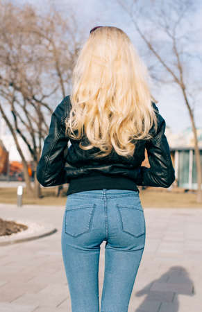girl ass: Pretty young fashion sexy girl with beautiful long blond hair on the road in evening summer time have fun and shows her nice back in jeans Stock Photo