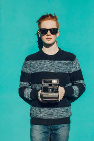 fashion portrait: Young redhead man in a sweater and jeans and sunglasses standing next to turquoise wall and taking photos vintage camera warm summer sunny day