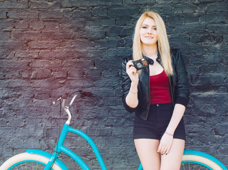 Portrait of a young beautiful blonde girl in a black jacket and shorts posing near the brick wall next to a bright blue vintage bicycle holding a vintage camera. Filter, light leak effect.