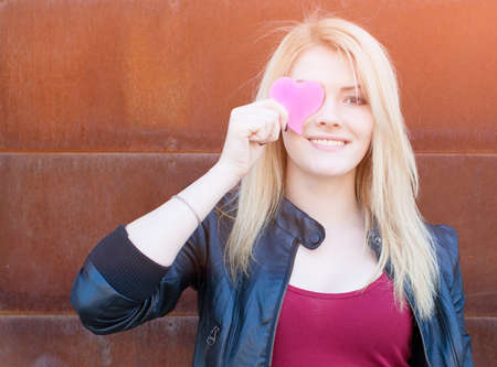 Portrait of a beautiful blonde girl with one hand closes the eyes pink paper heart