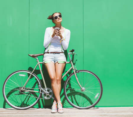 Pretty girl in shorts and t-shirt and sunglasses stands with  bicycle fix gear nex to green wall bright sunny day