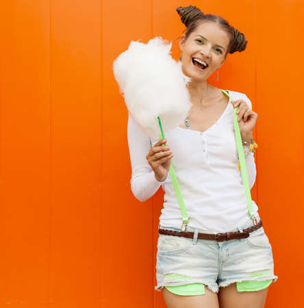 Beautiful fashionable girl with cotton candy posing nex to the orange wall photo