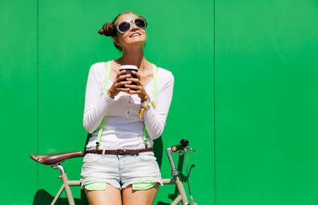 パンツと t シャツとクールなサングラス スタンド自転車の修正で、かわいい女の子は、緑の壁の明るい晴れた日に nex をギアします。