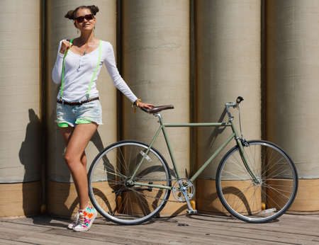 Pretty girl in shorts and t-shirt, in sunglasses stands with bicycle fix gear the posing against a background of an unusual wall of the huge pipes Banque d'images