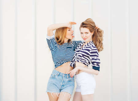 Portrait of two beautiful fashionable girlfriends in denim shorts and striped t-shirt posing nex to the glass wall. Girl stretches tongue to another, holding her by the hair. Outdoors. Warm colors. having fun and making funny faces. 版權商用圖片