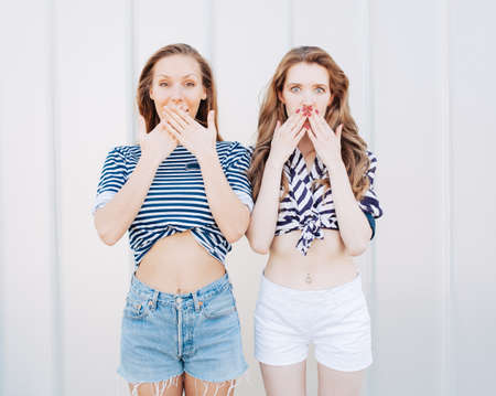 women friendship: Portrait of two beautiful fashionable girlfriends in denim shorts and striped t-shirt posing nex to the glass wall. Have positive surprised emotions, screaming and laughing, bright summer day.