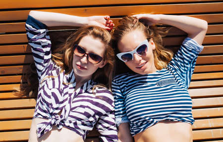 Close up lifestyle summer portrait of two girls friends relaxed and getting sunbathe, laying on the beach, wearing bright marine costumes and stylish sunglasses. 版權商用圖片