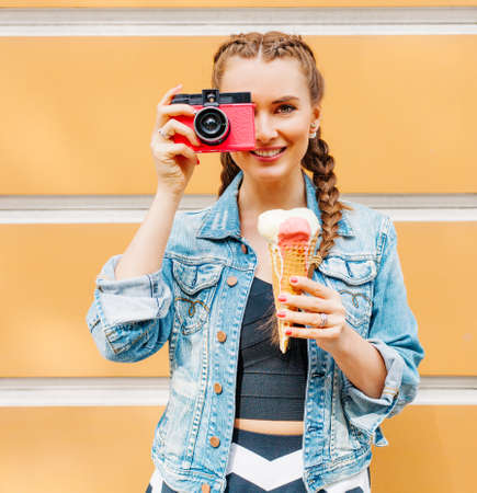 Beautiful fashionable young girl posing in a summer dress and denim jacket with pink vinage camera and multi-colored ice cream. Takes a picture. Outdoor