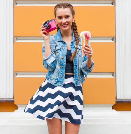 美しいファッショナブルな若い女の子はピンク vinage カメラとマルチカラーのアイス クリームで夏のドレスとデニム ジャケットのポーズします。屋