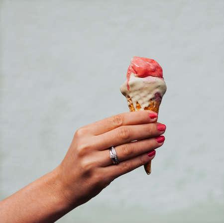 カラフルなアイス-クリーム コーンを保持している彼女の指にリングを持つ美しい女性の手。クローズ アップ。屋外。